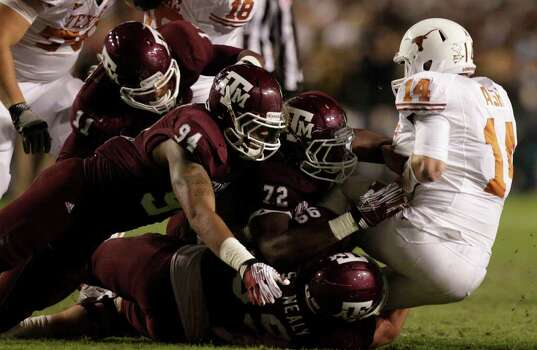 Texas quarterback David Ash (14) is stopped behind the line of scrimmage by a host of Texas A&M defenders during the first quarter of an NCAA college football game at Kyle Field Thursday, Nov. 24, 2011, in College Station. Photo: Brett Coomer, Houston Chronicle / © 2011 Houston Chronicle