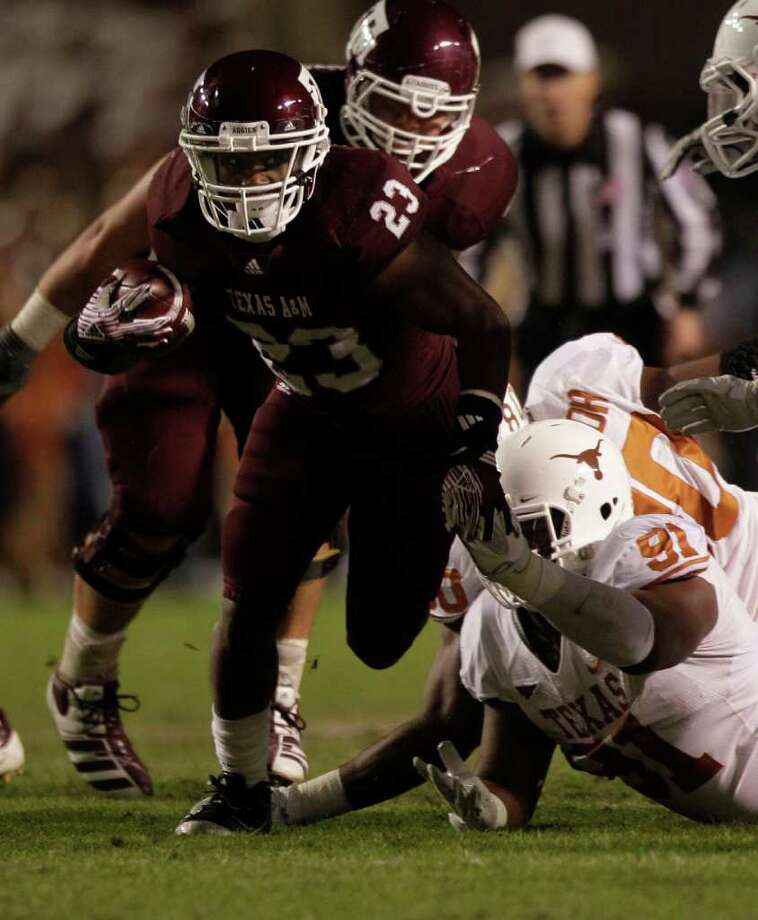 Texas A&M running back Ben Malena (23) runs past Texas defensive tackle Kheeston Randall (91) during the first quarter of an NCAA college football game at Kyle Field Thursday, Nov. 24, 2011, in College Station. Photo: Brett Coomer, Houston Chronicle / © 2011 Houston Chronicle