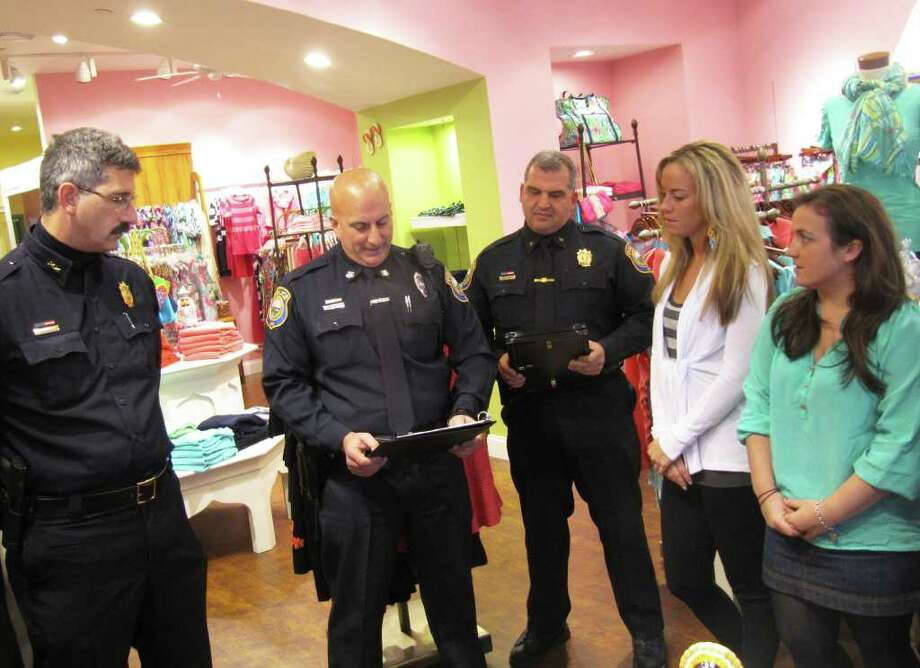 Westport Police Officer Peter Biagiotti, second from left, reads from a certificate of commendation during a press conference Wednesday morning in which Erin Meaney, second from right, and Marica Dacey, far right, were recognized for their role in helping to capture an out-of-state murder suspect on Nov. 9. Looking on is Police Chief Dale Call (far left) and Deputy Chief Foti Koskinas. Photo: Kirk Lang