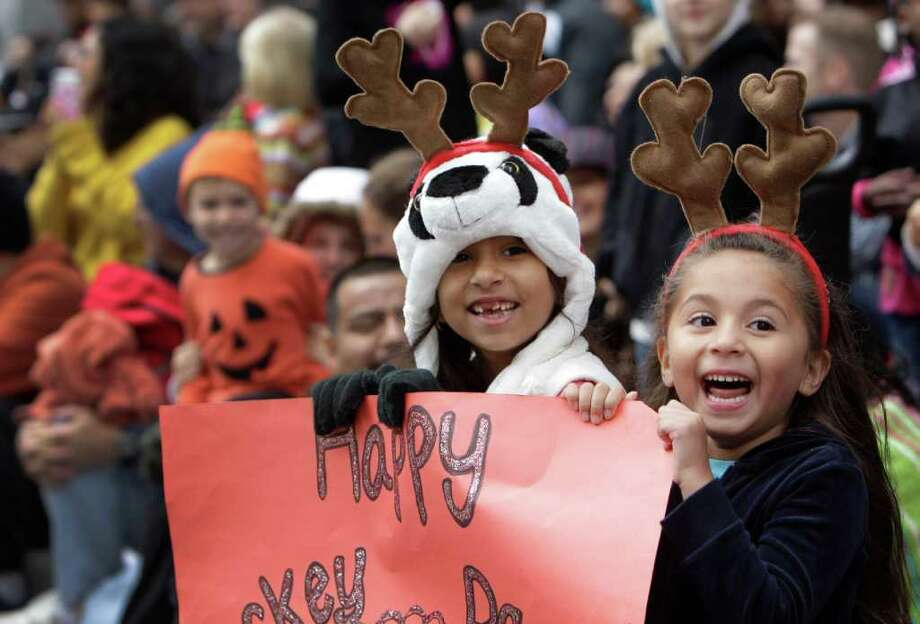 MELISSA PHILLIP PHOTOS : CHRONICLE SIGN OF THESE TIMES: Pricilla Medina, 7, left, and her cousin, Aaliyah Saiz, 4, wearing an assortment of holiday headgear, watch the 62nd Annual Holiday Parade on Thanksgiving Day in downtown Houston Thursday. They made a glitter sign that read Happy Turkey Day. Photo: Melissa Phillip / © 2011 Houston Chronicle