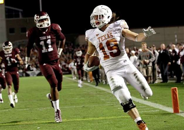 Texas' Blaine Irby (19) runs into the end zone after catching a pass for a touchdown as Texas A&M linebacker Jonathan Stewart (11) defends during the second quarter of an NCAA college football game, Thursday, Nov. 24, 2011, in College Station, Texas. (AP Photo/David J. Phillip) Photo: Associated Press