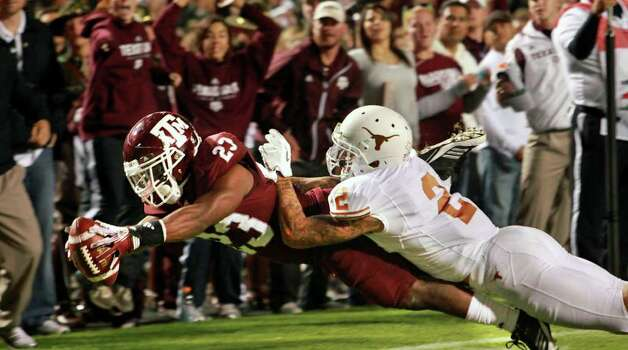 SPORTS   Ben Malena stretches out for the first Aggie touchdown , beating A.J. White to the end zone in the first quarter as Texas A&M hosts UT at Kyle Field in College Station on November 24, 2011.  Tom Reel/Staff Photo: TOM REEL, SAN ANTONIO EXPRESS-NEWS / © 2011 San Antonio Express-News