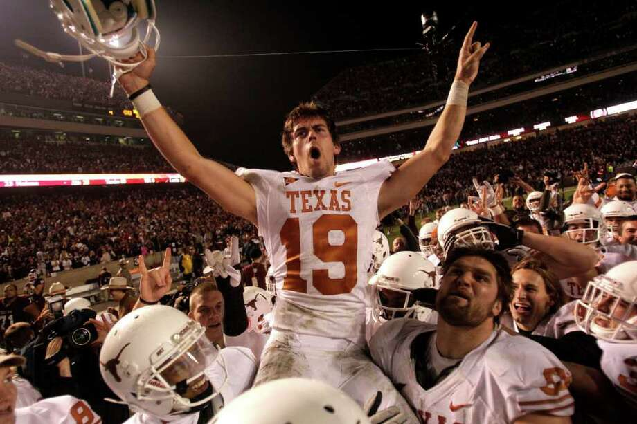 BRETT COOMER : CHRONICLE THE PRIZE OF TEXAS: Longhorns kicker Justin Tucker (19) is carried off the field by his teammates after kicking a last-second 40-yard field goal to beat Texas A&M on Thursday night in the 118th meeting - and for now, last - football game between the schools. Photo: Brett Coomer / © 2011 Houston Chronicle