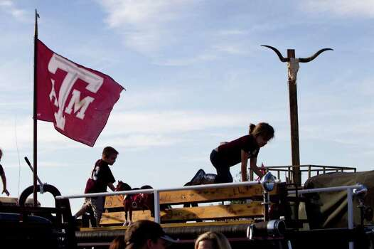Children play under a Texas A&M flag and a longhorn skull in the tailgating area before an NCAA college football game between Texas and Texas A&M at Kyle Field Thursday, Nov. 24, 2011, in College Station. Photo: Brett Coomer, Houston Chronicle / © 2011 Houston Chronicle