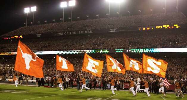 Flags spelling out Texas are run onto the field before an NCAA college football game between Texas A&M and Texas at Kyle Field Thursday, Nov. 24, 2011, in College Station. Photo: Brett Coomer, Houston Chronicle / © 2011 Houston Chronicle