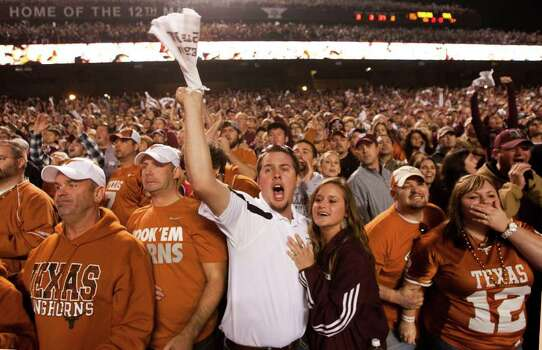 Texas fans Chad White and Shane White, left, of Corpus Christi,  Texas A&M fans Tyler Beam, center left, of Falls City, Genna Kopecki, of Karnes City, and Texas fans Chris and Shauna Stewart, far right, of Troup, react to a play near the end of the second quarter of an NCAA college football game at Kyle Field Thursday, Nov. 24, 2011, in College Station. Photo: Brett Coomer, Houston Chronicle / © 2011 Houston Chronicle