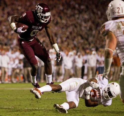Texas A&M wide receiver Jeff Fuller (8) leaps past Texas safety Christian Scott (6) for a 16-yard touchdown reception during the fourth quarter of an NCAA college football game at Kyle Field Thursday, Nov. 24, 2011, in College Station. Texas beat Texas A&M 27-25. Photo: Brett Coomer, Houston Chronicle / © 2011 Houston Chronicle