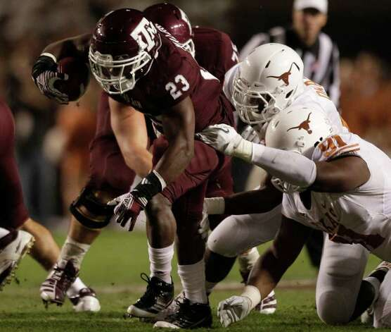 Texas A&M running back Ben Malena (23) is tackled by Texas defensive tackle Kheeston Randall (91) during the first quarter of an NCAA college football game at Kyle Field Thursday, Nov. 24, 2011, in College Station. Photo: Brett Coomer, Houston Chronicle / © 2011 Houston Chronicle