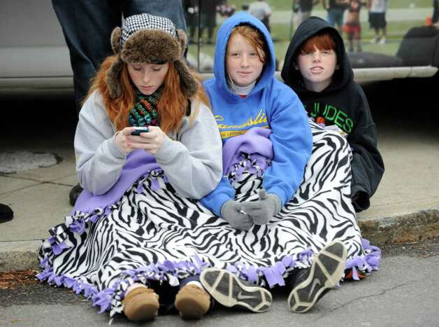 Sierra Owens, left, Sarafina French and Brody French use a blanket to keep warm beforethe 5K race during the Turkey Trot in Troy, N.Y. Nov. 24, 2011   (Skip Dickstein / Times Union) Photo: SKIP DICKSTEIN / 071120015A