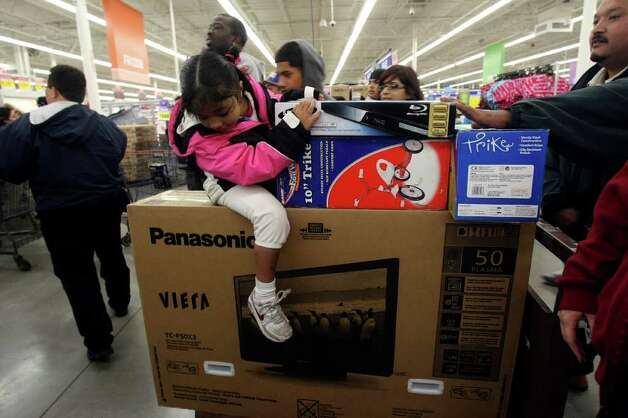 Alysiah Rendon, 5, rides on top of a 50-inch television as shoppers fill H-E-B Plus! for Black Friday sales on Friday, Nov. 25, 2011. More than 2,500 people lined up outside waiting for the doors to open at 4 a.m. Photo: HELEN L. MONTOYA, San Antonio Express-News / SAN ANTONIO EXPRESS-NEWS