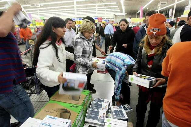 Shoppers grab tablets that were on sale for $45 at H-E-B Plus on Friday, Nov. 25, 2011. More than 2,500 people lined up outside waiting for the doors to open at 4 a.m. Photo: HELEN L. MONTOYA, San Antonio Express-News / SAN ANTONIO EXPRESS-NEWS