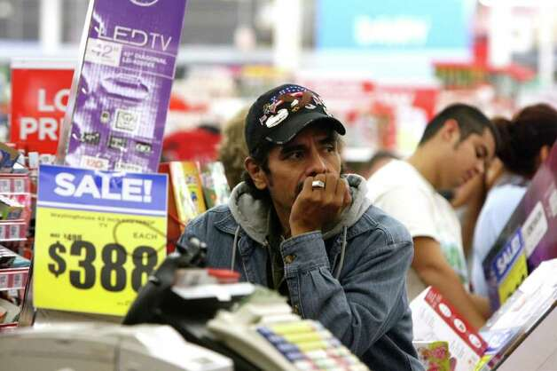 Alfred Zorola waits in line at H-E-B Plus! on Friday, Nov. 25, 2011. More than 2,500 people lined up outside waiting for the doors to open at 4 a.m for Black Friday sales. Photo: HELEN L. MONTOYA, San Antonio Express-News / SAN ANTONIO EXPRESS-NEWS