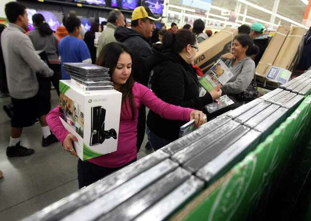 Anita Perez looks at DVDs after securing an XBox during the Black Friday sale on Friday, Nov. 25, 2011 at H-E-B Plus! Perez arrived at the store at 10 p.m. on Thursday. More than 2,500 people lined up outside waiting for the doors to open at 4 a.m. Photo: HELEN L. MONTOYA, San Antonio Express-News / SAN ANTONIO EXPRESS-NEWS