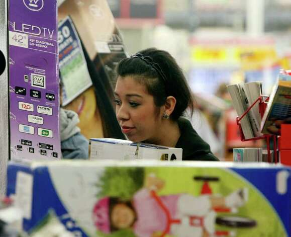 Nicole Navejar waits in line to purchase electronics at H-E-B Plus! on Friday, Nov. 25, 2011. More than 2,500 people lined up, waiting for the doors to open at 4 a.m. Photo: HELEN L. MONTOYA, San Antonio Express-News / SAN ANTONIO EXPRESS-NEWS