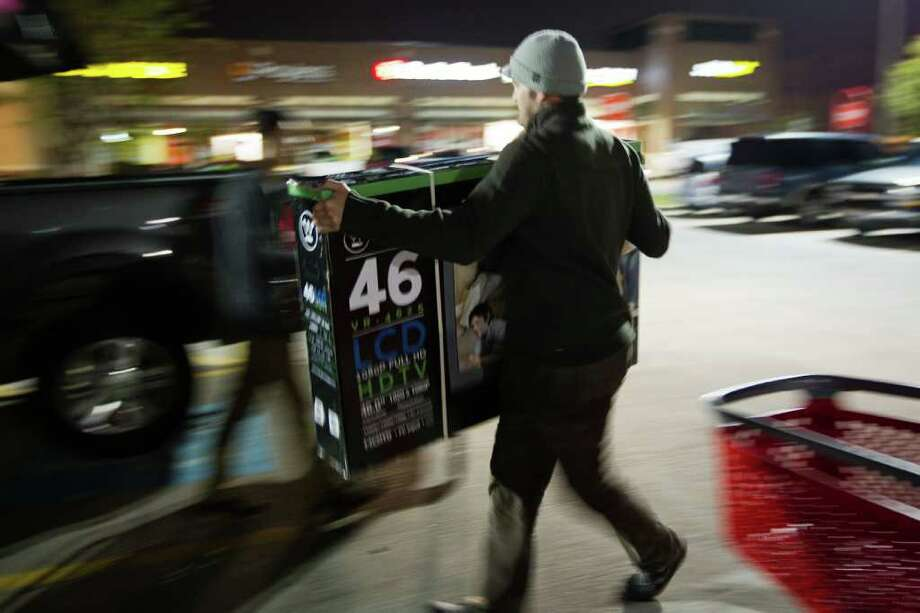 Black Friday shopper Kyle Curry loads his new flat screen television into his car at the Target Story on Sawyer Street near the downtown just after midnight on Friday, Nov. 25, 2011, in Houston. ( Smiley N. Pool / Houston Chronicle ) Photo: Smiley N. Pool / © 2011 Houston Chronicle