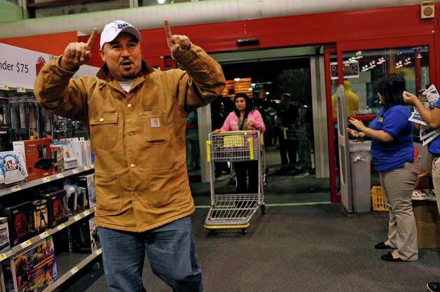 Roger Vargas (center) celebrates as he enters Best Buy as the store opens at midnight in San Antonio on Friday, Nov. 25,  2011. Vargas and his wife began waiting in line on Tuesday at 9 p.m. Photo: LISA KRANTZ, SAN ANTONIO EXPRESS-NEWS / SAN ANTONIO EXPRESS-NEWS