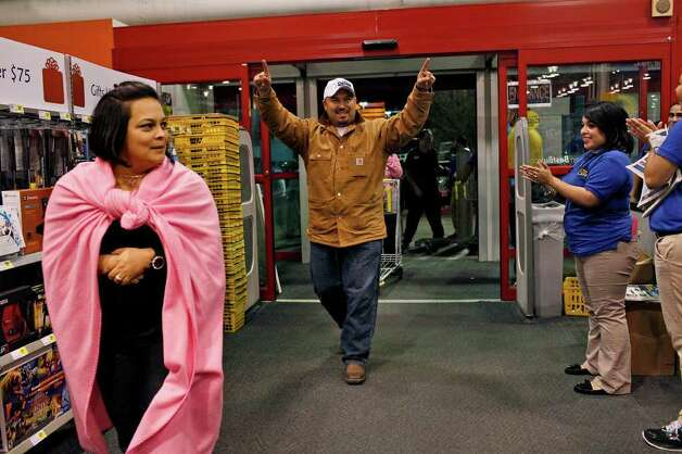 Roger Vargas (center) celebrates as he enters Best Buy with his wife, Martha Vargas (left), as the store opens at midnight in San Antonio on Friday, Nov. 25,  2011. The couple began waiting in line on Tuesday at 9 p.m. Photo: LISA KRANTZ, SAN ANTONIO EXPRESS-NEWS / SAN ANTONIO EXPRESS-NEWS