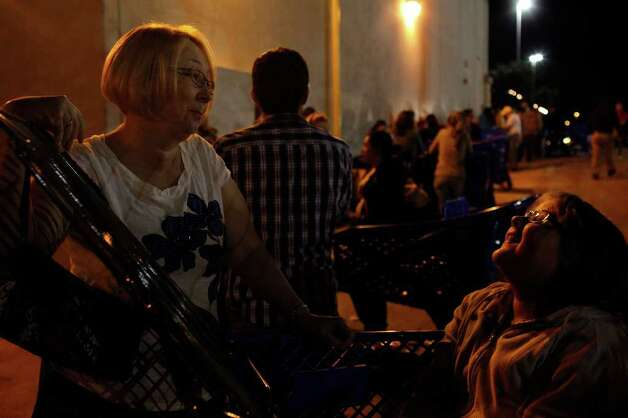 "Crystal Kopecki, 13 (right), sits in a cart as she waits with her aunt, Leslie Thayer-Coleman (left), to buy a Xbox 360 at the Toys ""R"" Us and Babies ""R"" Us store in San Antonio on Thursday, Nov. 24, 2011. Photo: LISA KRANTZ, SAN ANTONIO EXPRESS-NEWS / SAN ANTONIO EXPRESS-NEWS"