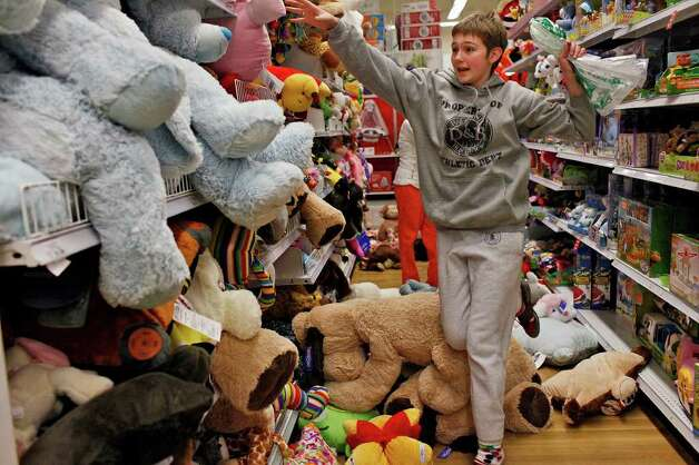 "Marah Aylor, 14, tries to find a stuffed animal at the Toys ""R"" Us and Babies ""R"" Us store in San Antonio on Thursday, Nov. 24,  2011. ""I collect them, they make me happy,"" Aylor said. Photo: LISA KRANTZ, SAN ANTONIO EXPRESS-NEWS / SAN ANTONIO EXPRESS-NEWS"