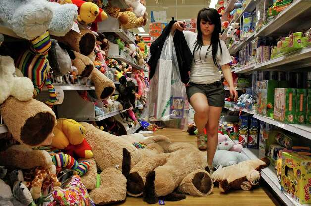 "Brittany Flores steps over stuffed animals as she shops at the Toys ""R"" Us and Babies ""R"" Us store after the 9 p.m. opening in San Antonio on Thursday, Nov. 24,  2011. Photo: LISA KRANTZ, SAN ANTONIO EXPRESS-NEWS / SAN ANTONIO EXPRESS-NEWS"