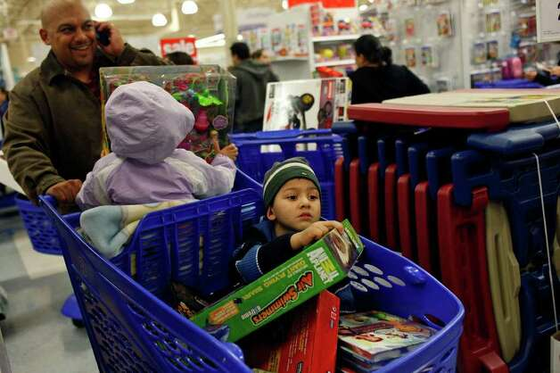 "Patrick Fernandez, Jr., 4, and his sister, Bella Fernandez, 3, shop with their father, Patrick Fernandez, all of Houston, at the Toys ""R"" Us and Babies ""R"" Us store in San Antonio on Thursday, Nov. 24,  2011. Photo: LISA KRANTZ, SAN ANTONIO EXPRESS-NEWS / SAN ANTONIO EXPRESS-NEWS"