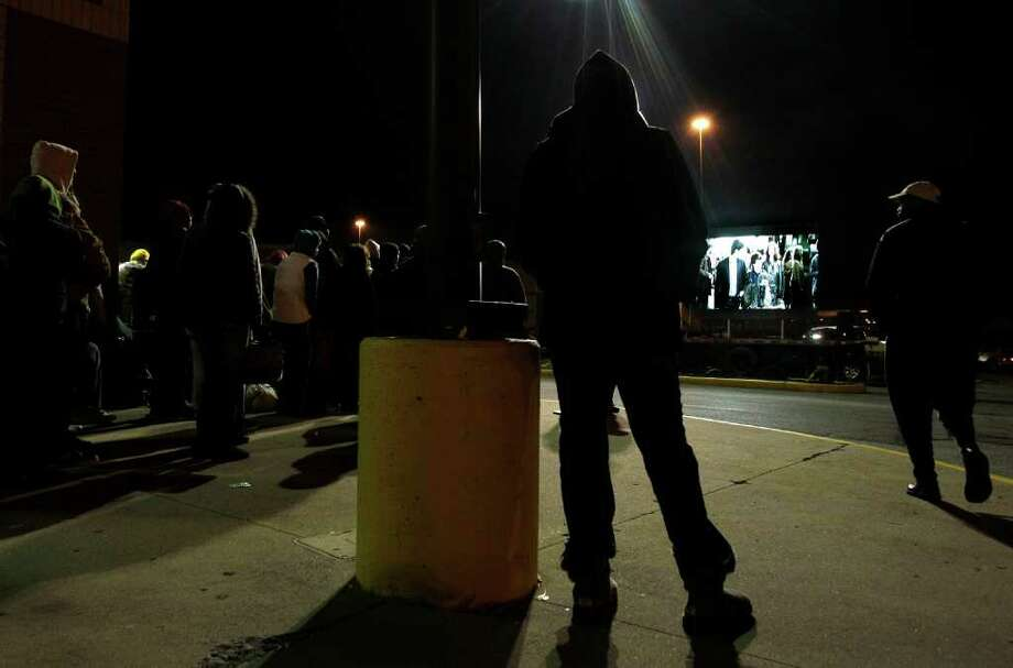 Early bird shoppers watch a Harry Potter movie being shown on a giant screen outside the Best Buy store in Mayfield Hts., Ohio while waiting for the doors to open at midnight on Thursday, Nov. 24, 2011. This weekend, many stores will for the first time use midnight openings along with the usual bevy of deals as they try to lure consumers, whose appetite for good-buys has been increasing since the Great Recession. (AP Photo/Amy Sancetta) Photo: Amy Sancetta / AP