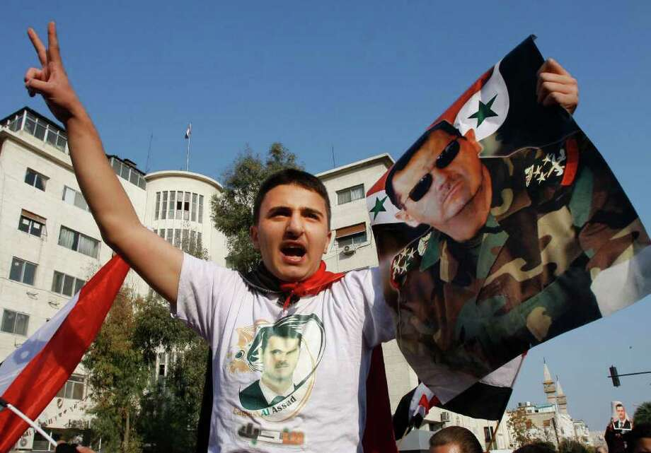 A pro-Syrian regime protester shouts slogans and holds up a portrait of the Syrian president Bashar Assad during a protest against the Arab League decisions, in Damascus, Syria, on Friday Nov. 25, 2011. Syria missed an Arab League deadline Friday to allow hundreds of observers into the country, prompting the bloc to consider economic sanctions against Damascus for its eight-month crackdown on dissent, a senior diplomat said. (AP Photo/Muzaffar Salman) Photo: Muzaffar Salman / AP