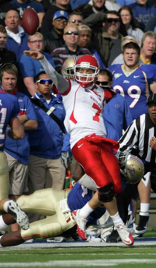 University of Houston quarterback Case Keenum (7) flips the ball out of bounds as University of Tulsa defensive end Tyrunn Walker (94) tries to pull him down during the first quarter of a NCAA football game, Friday, Nov. 25, 2011, in H.A. Chapman Stadium in Tulsa. Photo: Nick De La Torre, Houston Chronicle / © 2011  Houston Chronicle