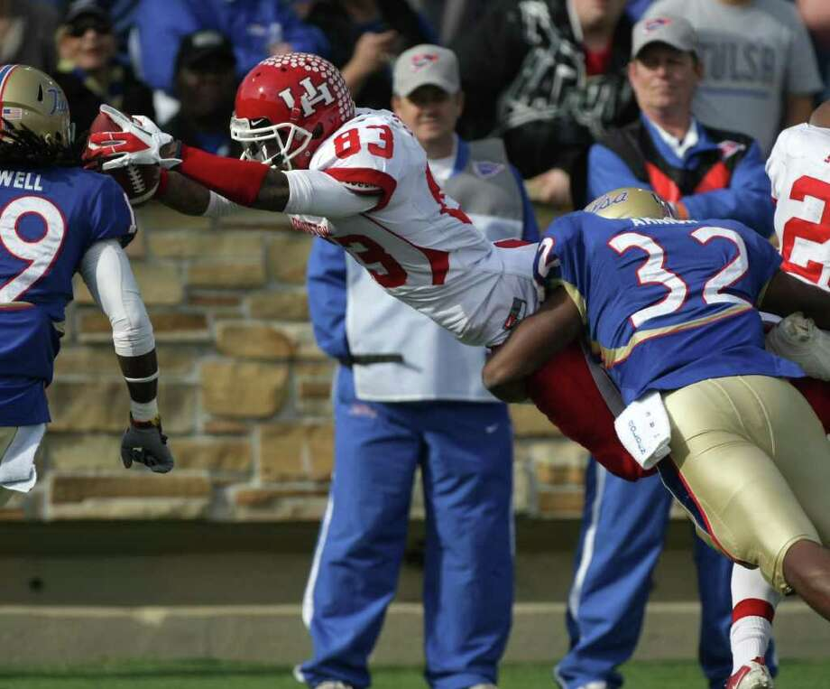 University of Houston wide receiver Patrick Edwards (83) dives past ]University of Tulsa linebacker Curnelius Arnick (32) for a touchdown during the first quarter of a NCAA football game, Friday, Nov. 25, 2011, in H.A. Chapman Stadium in Tulsa. Photo: Nick De La Torre, Houston Chronicle / © 2011  Houston Chronicle