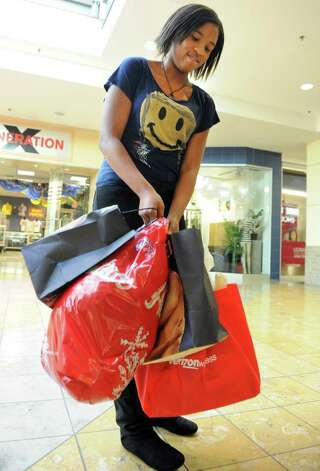 Fifteen-year-old Tamai Randolph, of West Haven, adjusts her baggage after a day of shopping at The Westfield Connecticut Post Mall on Black Friday, Nov. 25, 2011.  Randolph arrived to the mall at 6 am. Photo: Autumn Driscoll / Connecticut Post