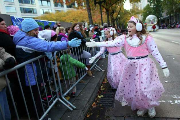 Participants greet the crowd during the Macy's Holiday Parade on Friday in downtown Seattle. Crowds lined downtown streets to see the annual parade. Photo: JOSHUA TRUJILLO / SEATTLEPI.COM