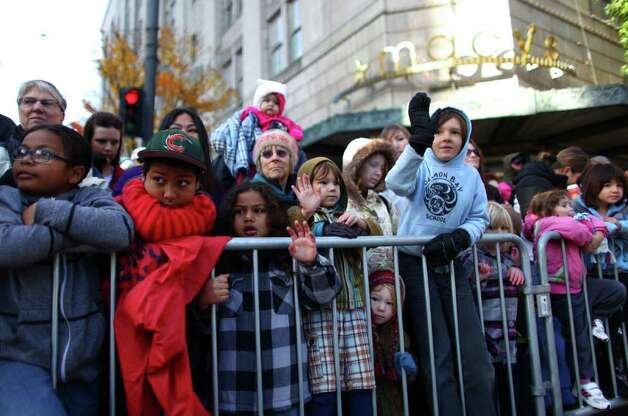 Spectators attend the Macy's Holiday Parade on Friday in downtown Seattle. Crowds lined downtown streets to see the annual parade. Photo: JOSHUA TRUJILLO / SEATTLEPI.COM