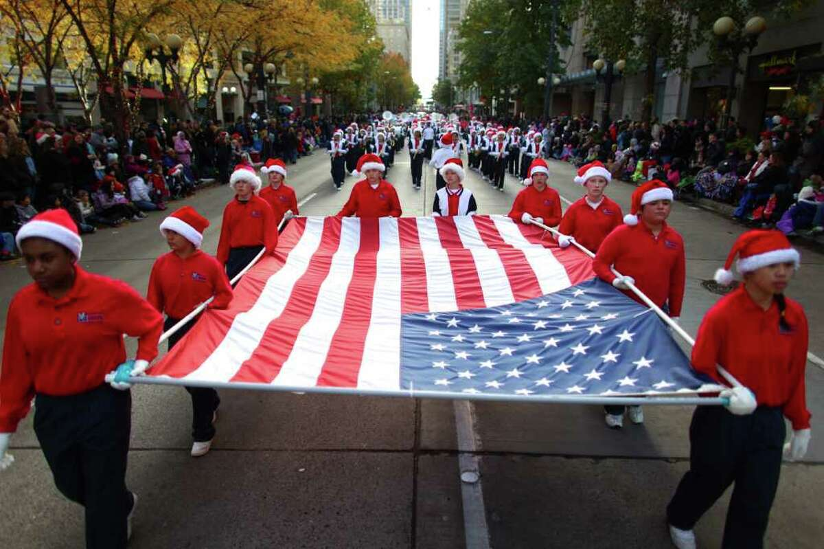 Students from Explorer Middle School in Mukilteo carry a flag during the Macy's Holiday Parade on Friday in downtown Seattle. Crowds lined downtown streets to see the annual parade.
