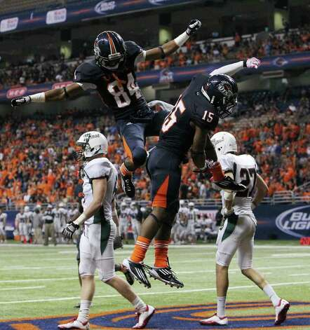 UTSA's Brandon Freeman (84) and Josiah Monroe (15) celebrate a second half touchdown by Freeman against Minot at the Alamodome on Saturday, Nov. 19, 2011. UTSA defeated Minot 49-7 for a victory to end their inaugural season. Kin Man Photo: Kin Man Hui, SAN ANTONIO EXPRESS-NEWS / San Antonio Express-News