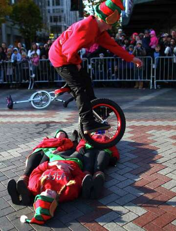 A member of the Panther Pride unicycle team leaps over teammates during the Macy's Holiday Parade on Friday in downtown Seattle. Crowds lined downtown streets to see the annual parade. Photo: JOSHUA TRUJILLO / SEATTLEPI.COM