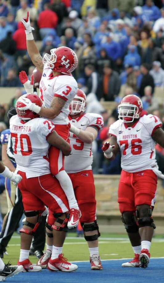 University of Houston wide receiver Justin Johnson (3) is held up by offensive linesman Chris Thompson (70) after he made a wide open catch for a touchdown during the fourth quarter of a NCAA football game against the University of Tulsa, Friday, Nov. 25, 2011, in H.A. Chapman Stadium in Tulsa. The University of Houston won 48-16. Photo: Nick De La Torre, Houston Chronicle / © 2011  Houston Chronicle