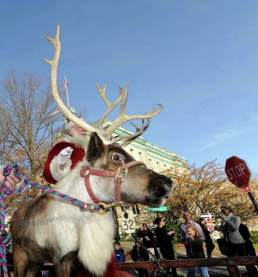 A reindeer parades down Greenwich Avenue with Santa during the McArdle's Florist & Garden Center's third annual Greenwich Reindeer Festival and Santa's Workshop Friday afternoon, Nov. 25, 2011. Photo: Bob Luckey / Greenwich Time
