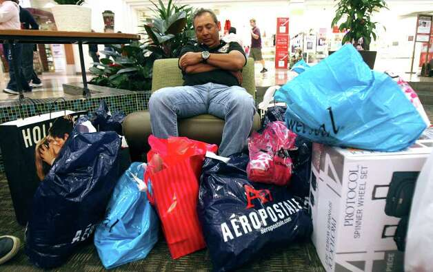 Javier Vargas guards his family's purchases on Friday, Nov. 25, 2011 at North Star Mall.  Vargas said he arrived at the mall at midnight. Photo: HELEN L. MONTOYA, San Antonio Express-News / SAN ANTONIO EXPRESS-NEWS