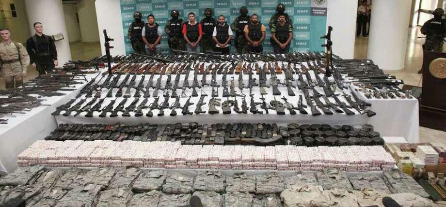 Autoridades mexicanas arrestaron a cinco presuntos miembros del grupo de narcotraficantes de los Zetas cerca de Villa Unión y los presentaron ante la prensa junto a un cargamento de uniformes militares, municiones y más de 200 armas de fuego, el 9 de junio de 2011 en México D.F. Photo: Alexandre Meneghini / AP