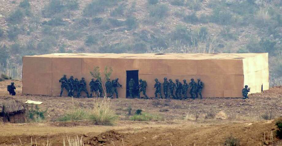 B.K. BANGASH : ASSOCIATED PRESS PRACTICE: Pakistani and Chinese soldiers storm a hideout during a joint drill in Pakistan.  China is looking to fill the void that may develop if the U.S. and Pakistan are estranged. Photo: B.K.Bangash / AP