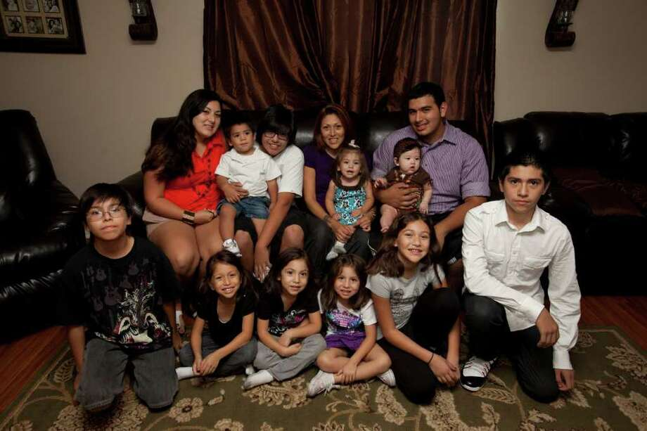 The Perales family, from left front: Daniel, 11; Juliet, 5; Clarissa and Sophia, 4; Danielle, 10; and Julian, 14. From left rear: Jackie, 22; Aidan, 2; Michael, 16; their mother, Lori, with Bella, 1; and Anneliese, 6 months, held by her oldest brother, Arnie, 19. Photo: Eric Kayne / © 2011 Eric Kayne