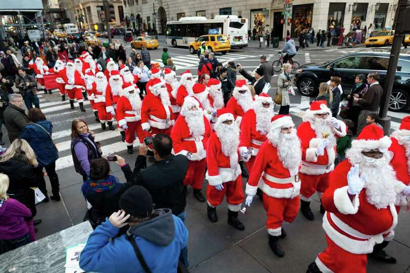 Charity workers dressed as Santa Claus walk up Fifth Avenue during a march of Sidewalk Santas, Frida