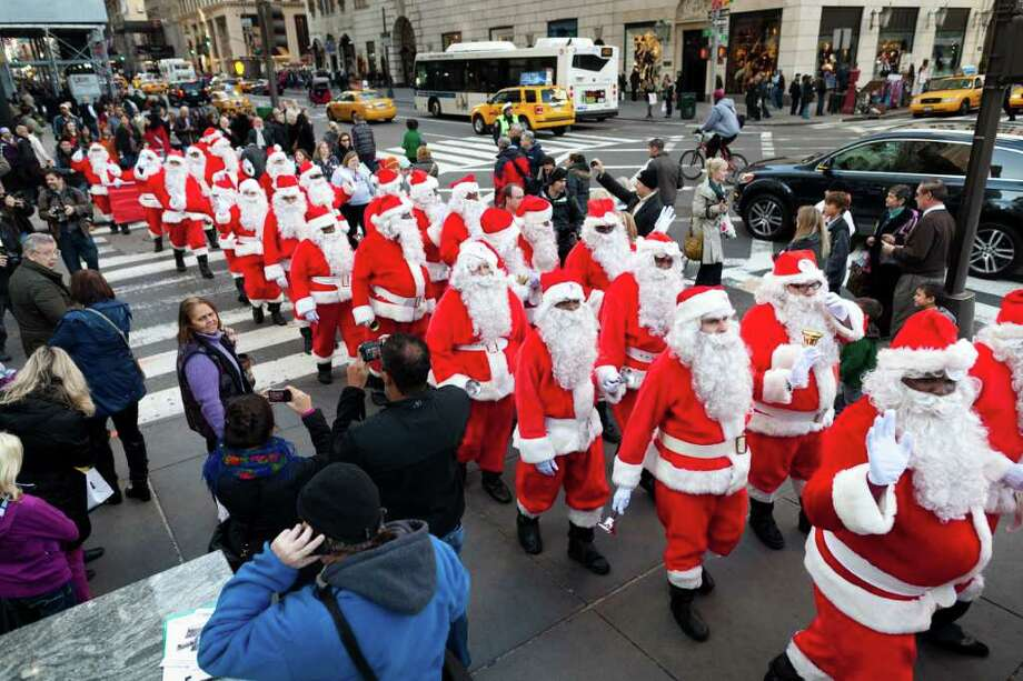 Charity workers dressed as Santa Claus walk up Fifth Avenue during a march of Sidewalk Santas, Friday, Nov. 25, 2011, in New York. Volunteers of America held it's 109th annual Sidewalk Santa Parade on the busiest shopping day of the year to raise money for a holiday food voucher program for needy residents. Photo: John Minchillo, Associated Press / FR170537 AP