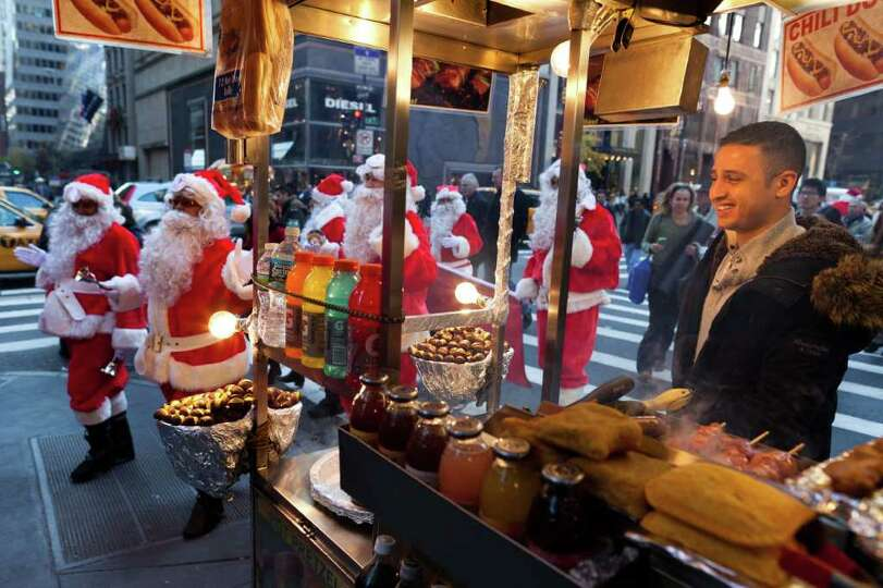 A street vendor smiles as charity workers dressed as Santa Claus pass by on Fifth Avenue.