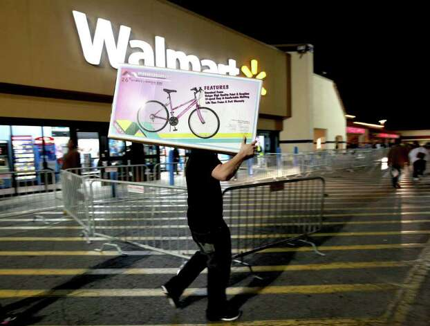 A shopper walks to his car after purchasing a bike at Walmart in Butler Plaza on Thursday, Nov. 24, 2011, in Gainesville, Fla. Walmart opened stores on Thursday. Photo: AP