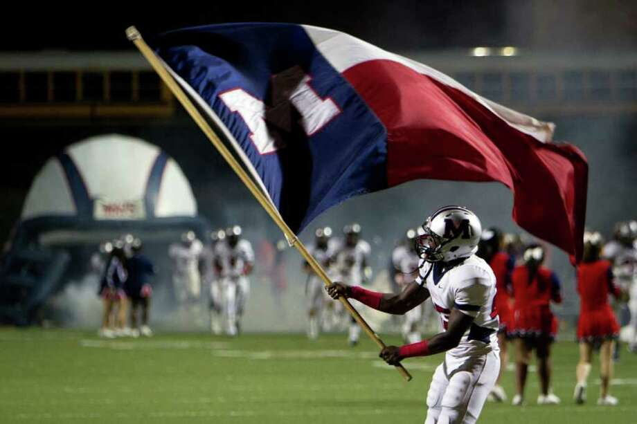 Manvel wide receiver Corey Seymour waves the school flag as the teams take the field before playing Dayton in a Class 4A Div. II Region III semifinals high school playoff game at Abshier Stadium Friday, Nov. 25, 2011, in Deer Park. Photo: Smiley N. Pool, Houston Chronicle / © 2011  Houston Chronicle