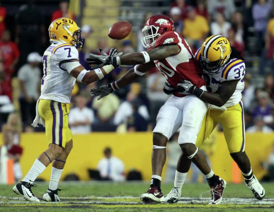 MICHAEL WESTBROOK: ASSOCIATED PRESS QUICK HANDS: LSU's Tyrann Mathieu, left, grabs the ball after knocking it away from Arkansas tight end Chris Gragg, center, as Karnell Hatcher tries to bring down  Gragg. Photo: Michael Westbrook / The Daily Advertiser