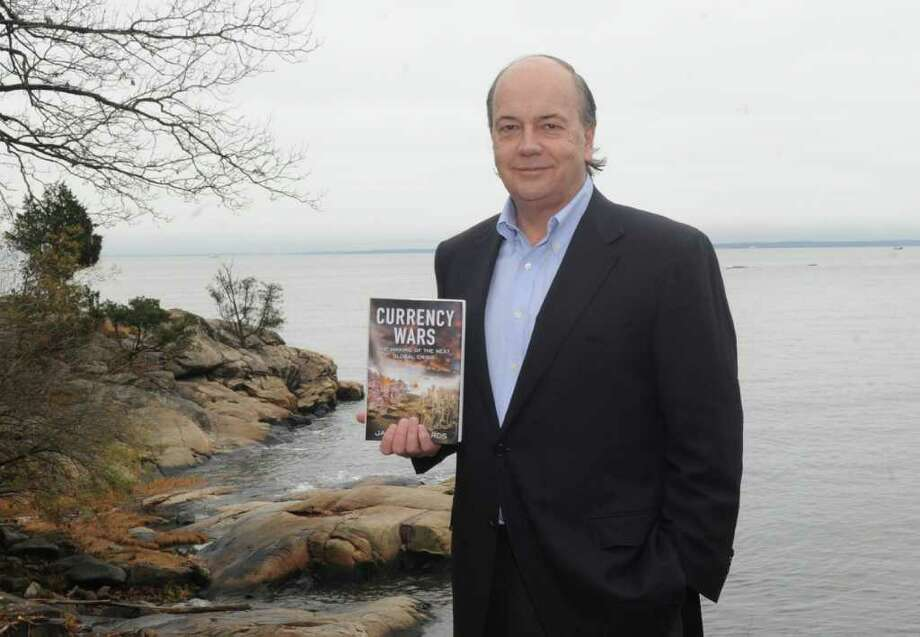 "Jim Rickards, author of ""Currency Wars,"" with his book at his home in Darien Wednesday, Nov. 23, 2011. Photo: Helen Neafsey / Greenwich Time"