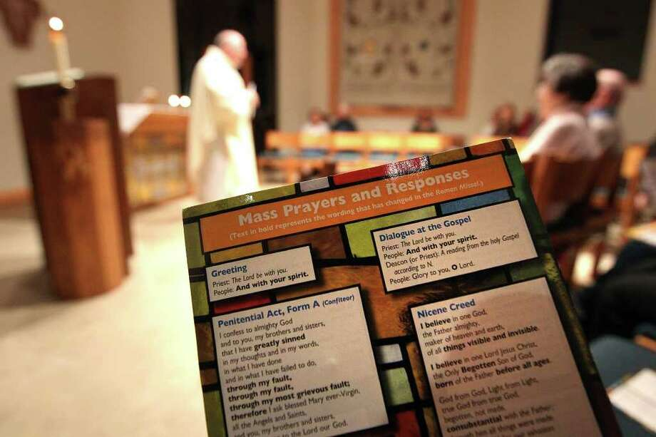 A card is offered for parishioners to follow along during an evening Mass at St. Francis of Assisi Catholic Church on Wednesday, Nov. 23, 2011. The church will be using a revised Roman Missal for Mass services starting Sunday. Kin Man Hui/kmhui@express-news.net Photo: KIN MAN HUI, SAN ANTONIO EXPRESS-NEWS / SAN ANTONIO EXPRESS-NEWS