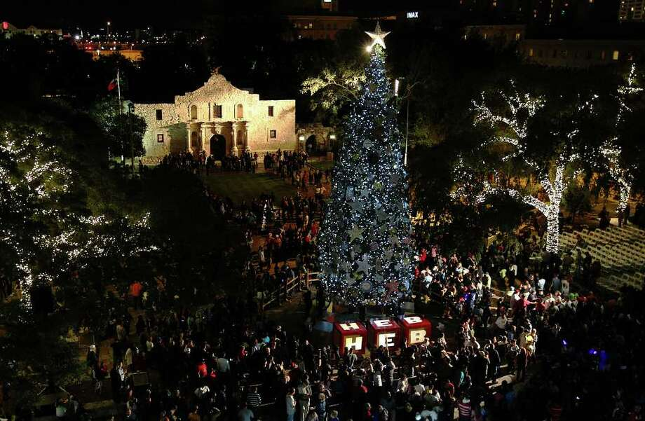 People gather around the 55-foot tall Christmas Tree after the lights were turned on during the H-E-B Tree Lighting Celebration at Alamo Plaza on Friday, Nov. 25, 2011. Thousands of LED lights were used to light the tree as well as the surrounding holiday decorations. Photo: KIN MAN HUI, SAN ANTONIO EXPRESS-NEWS / SAN ANTONIO EXPRESS-NEWS